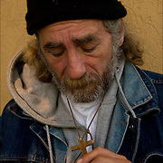 Portrait of Mark, a homeless person on the Atlantic City Boardwalk in November holding crucifix in hand with painful expression on his face. He has found faith in religion on the streets.<br />