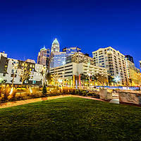 Charlotte North Carolina skyline at night photo with Romare Bearden Park and downtown Charlotte buildings against a blue sky. Charlotte is a major city in North Carolina in the Eastern United States.