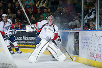 KELOWNA, CANADA - NOVEMBER 28: Eric Comrie #1 of the Tri City Americans passes the puck behind the net at the Kelowna Rockets on November 28, 2012 at Prospera Place in Kelowna, British Columbia, Canada (Photo by Marissa Baecker/Shoot the Breeze) *** Local Caption ***