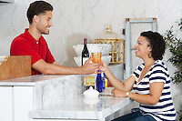 Woman handing over empty glass to male waiter at counter