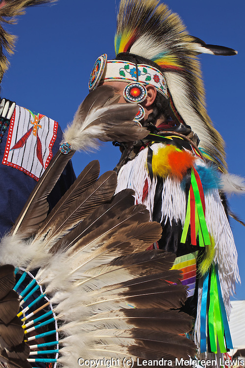 Photo of two Native American men dressed in regalia talking on the sidelines of dance arena.