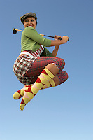 Portrait of young woman jumping with golf club