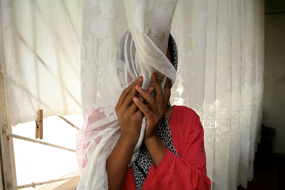 Girl hiding behind a curtain in Kokand