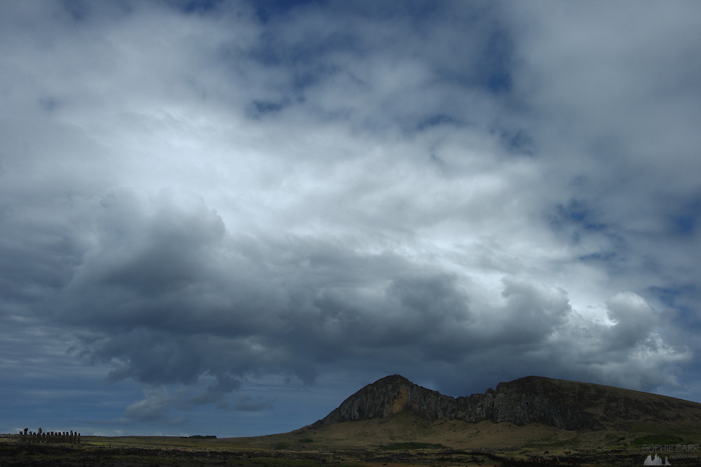 Big clouds gather of Rano Raraku, a large volcanic crater on Easter Island. To the left is Tongariki ahu with fifteen moais standing, facing inwards