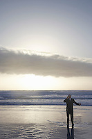Business man using mobile phone standing in sea at sunset elevated view