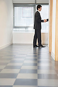 Businessman Shaking Hands through doorway with unseen person side view