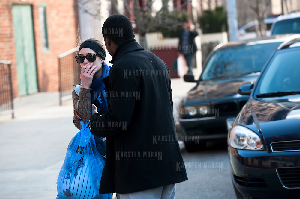 March 13, 2013 - New York, NY : Images from the scene at 102 Bradhurst Avenue (The Sutton), near W. 147th Street, where a woman and her infant child fell from an eighth story window on Wednesday afternoon. Matthew Rue, right,  who lives in the first floor of the building, and his girlfriend Liz Sierra, left, react as they near the scene. CREDIT: Karsten Moran for The New York Times