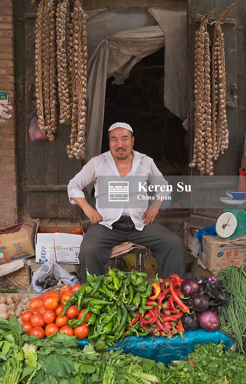 Uighur man selling vegetable at Sunday Market, Kashgar, Xinjiang, Silk Road, China