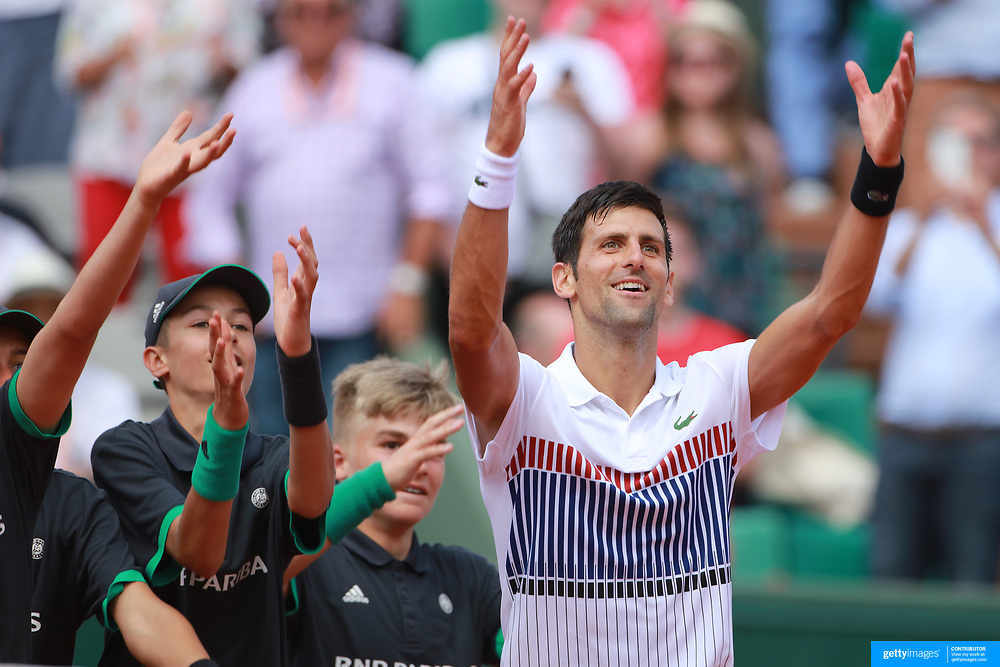 2017 French Open Tennis Tournament - Day Four.  Novak Djokovic of Serbia celebrate his win against Joao Sousa of Portugal with the ball boys and girls on Court Suzanne Lenglen in the Men's Singles second round match match at the 2017 French Open Tennis Tournament at Roland Garros on May 31st, 2017 in Paris, France.  (Photo by Tim Clayton/Corbis via Getty Images)