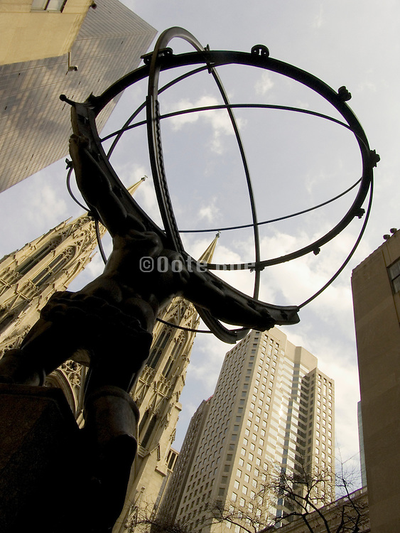 A statue of a man Atlas holding the earth in front of Saint Patrick?s Cathedral NY