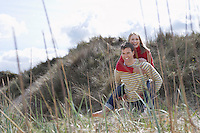 Man giving woman piggy back on dunes