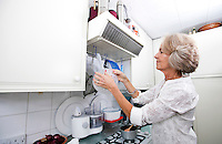 Senior woman hanging colander in domestic kitchen
