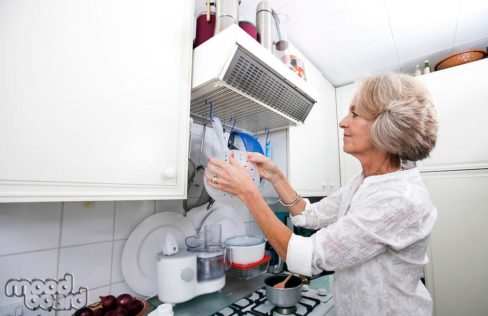 Senior woman hanging colander in domestic kitchen