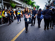 13 OCTOBER - BANGKOK, THAILAND: A woman carries a portrait of the late king on the first anniversary of the death of Bhumibol Adulyadej, the Late King of Thailand. About 199 monks from 14 Buddhist temples in Bangkok participated in the mass merit making at Siriraj Hospital to mark the anniversary of the revered King's death. He will be cremated on 26 October 2017.  PHOTO BY JACK KURTZ