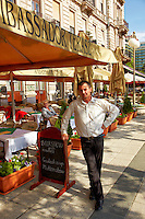 View of a waiter standing outside of the Ambassador Terasz Restaurant, Budapest, Hungary.
