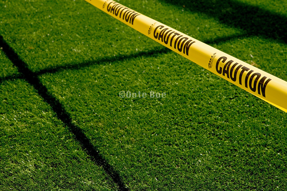 fresh rolled out grass with yellow warning caution tape