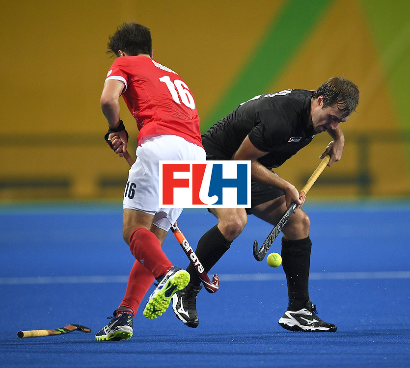 Britain's Adam Dixon (L) vies for the ball with New Zealand's Nic Woods during the men's field hockey Britain vs New Zealand match of the Rio 2016 Olympics Games at the Olympic Hockey Centre in Rio de Janeiro on August, 7 2016. / AFP / MANAN VATSYAYANA        (Photo credit should read MANAN VATSYAYANA/AFP/Getty Images)