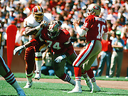 San Francisco 49ers quarterback Joe Montana (16) drops back to pass while 49ers offensive tackle Steve Wallace (74) blocks high stepping Washington Redskins defensive end Charles Mann (71) during the 1990 NFL regular season football game against the Washington Redskins on Sept. 16, 1990 in San Francisco. The 49ers won the game 26-13. (©Paul Anthony Spinelli)