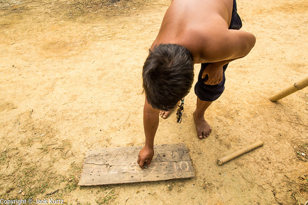 12 MARCH 2013 - ALONG HIGHWAY 13, LAOS:  A man keeps score during a bocce ball game on the side of Highway 13. Bocce ball was brought to Laos by the French. The paving of Highway 13 from Vientiane to near the Chinese border has changed the way of life in rural Laos. Villagers near Luang Prabang used to have to take unreliable boats that took three hours round trip to get from the homes to the tourist center of Luang Prabang, now they take a 40 minute round trip bus ride. North of Luang Prabang, paving the highway has been an opportunity for China to use Laos as a transshipping point. Chinese merchandise now goes through Laos to Thailand where it's put on Thai trains and taken to the deep water port east of Bangkok. The Chinese have also expanded their economic empire into Laos. Chinese hotels and businesses are common in northern Laos and in some cities, like Oudomxay, are now up to 40% percent. As the roads are paved, more people move away from their traditional homes in the mountains of Laos and crowd the side of the road living off tourists' and truck drivers.    PHOTO BY JACK KURTZ