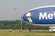 Montgomery, NY - Members of the ground crew, including one man on the mooring mast, prepare the Met Life blimp Snoopy Two for take off from Orange County Airport as a helicopter flies by in the background on July 26, 2008.