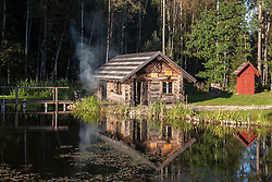 Old wooden smoke sauna in Sokka holiday resort in Estonia. Reflection on water, red outhouse.