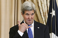 "U.S. Secretary of State John Kerry makes the ""call me"" signal to someone in the audience as he plays host to a luncheon celebrating recipients of the Art in Embassies Medal of Arts Award at the State Department in Washington."