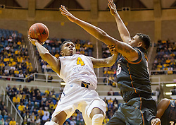 West Virginia Mountaineers guard Daxter Miles Jr. (4) adjusts and makes a shot against the Texas Longhorns during the first half at the WVU Coliseum.
