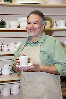 Happy potter with clay cup and saucer in pottery workshop