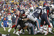 Bills running back Travis Henry (20) takes a low hit from Dolphins linebacker Junior Seau (55) and a high hit from linebacker Zach Thomas (54) while rushing for only 67 yards on 24 carries during a 20 to 3  win by the Miami Dolphins over the Buffalo Bills in an NFL Week 16 game in Buffalo on December 21, 2003. ©Paul Anthony Spinelli