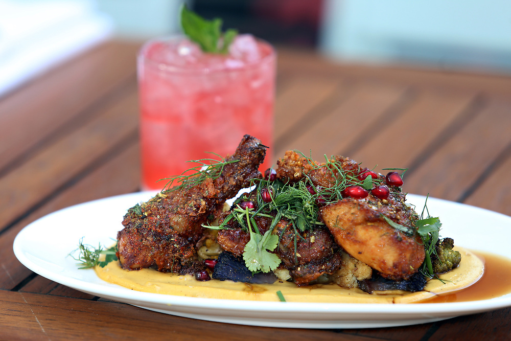 Buttermilk fried chicken over fenugreek cauliflower, pomegranate and green herbs with a Spring Fling--Crop cucumber vodka, cranberry, lemon and fresh mint. Outside dining at the Upsider, 1004 2nd Ave. (at 53rd Street), Monday, April 6, 2015. (Alexander Cohn for New York Daily News)