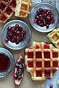 Fresh baked waffle topped with pomegranate sorbet and pomegranate seeds on silver plates.