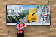 "Ready for the mountain? A backpacker points to an imagined elbow owie. ""Mountain Hiking - but Safe"" campaign (sponsored by SWICA, one of Switzerland's leading health and accident insurers): www.sicher-bergwandern.ch. Lauterbrunnen village is in the canton of Bern, Switzerland, the Alps, Europe. For licensing options, please inquire."