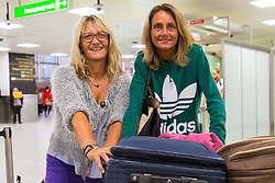 Melanie Cook, 55, left, and friend Caroline Ives, 53, arrive back at Gatwick Airport on one of the first repatriation flights for stranded Thomas Cook clients, from Dalaman in Turkey. Travel company Thomas Cook has ceased trading after failing to come to a deal with its bankers and creditors, leaving tens of thousands of travellers unable to depart on their holidays from South Terminal at Gatwick Airport, and a massive repatriation exercise to return holidaymakers from destinations all over the world. London Gatwick Airport, September 23 2019.