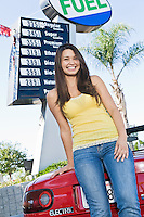 Portrait of smiling woman standing by electric car at gas station