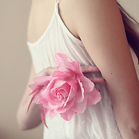 girl holding a pink rose behind her back
