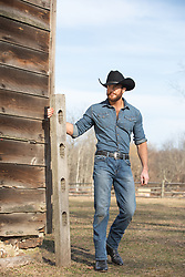 cowboy walking by a barn