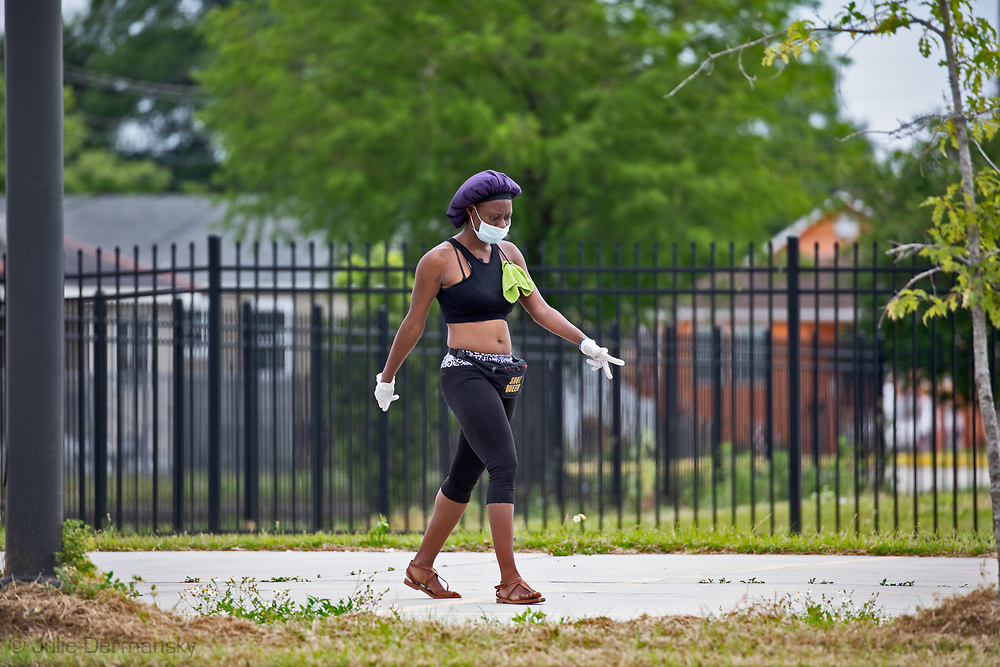 New Orleans,  April 4, 2020,  Woman  wearing gloves and a mask walking through the Lower Ninth Ward, as the Coronavirus continues to spread globaly.