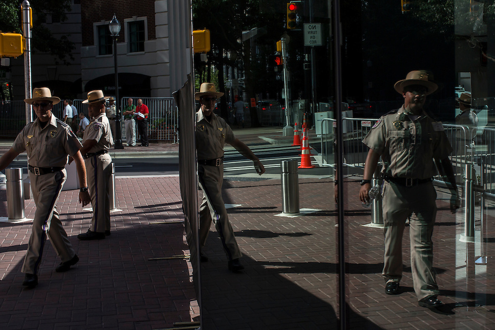 Police officers are reflected in a window in the uptown area on Sunday, September 2, 2012 in Charlotte, NC.