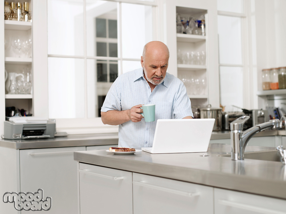 Middle-aged man in kitchen using laptop and holding coffee cup