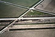 Nederland, Zuid-Holland, Hoeksche Waard, 08-03-2002; detail van het trace; midden en vlnr de werkweg  van de HSL met spoorsloten aan weerszijden, toekomstige aardebaan komt naast werkweg; diagonaal de Eerste Kruisweg (van linksboven naar midden rechts, zie ook overzichtsfoto) welke kruist met de Lange Dam (diagonaal links onder recht boven). Deze laatste weg is afgesloten voor lokaal verkeer tgv de bouw van de lijn; infrastructuur verkeer en vervoer spoor bouw landschap;<br /> luchtfoto (toeslag), aerial photo (additional fee)<br /> foto /photo Siebe Swart