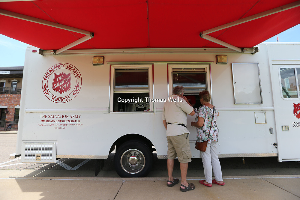 Jon and Eva Lueckel of Hamburg Germany get a free hot dog from the Salvation Army food truck that spent the lunch hour on Wednesday giving away free food at Fairpark in Tupelo.
