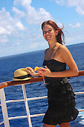 woman drinks cocktails  on a deck of a cruise ship