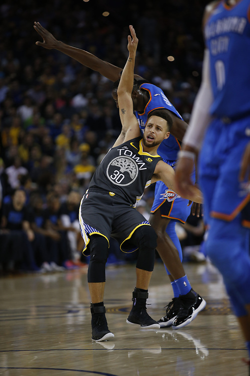 Golden State Warriors guard Stephen Curry (30) loses his balance during the first half of an NBA game between the Warriors and Oklahoma City Thunder at Oracle Arena, Tuesday, Feb. 6, 2018, in Oakland, Calif.