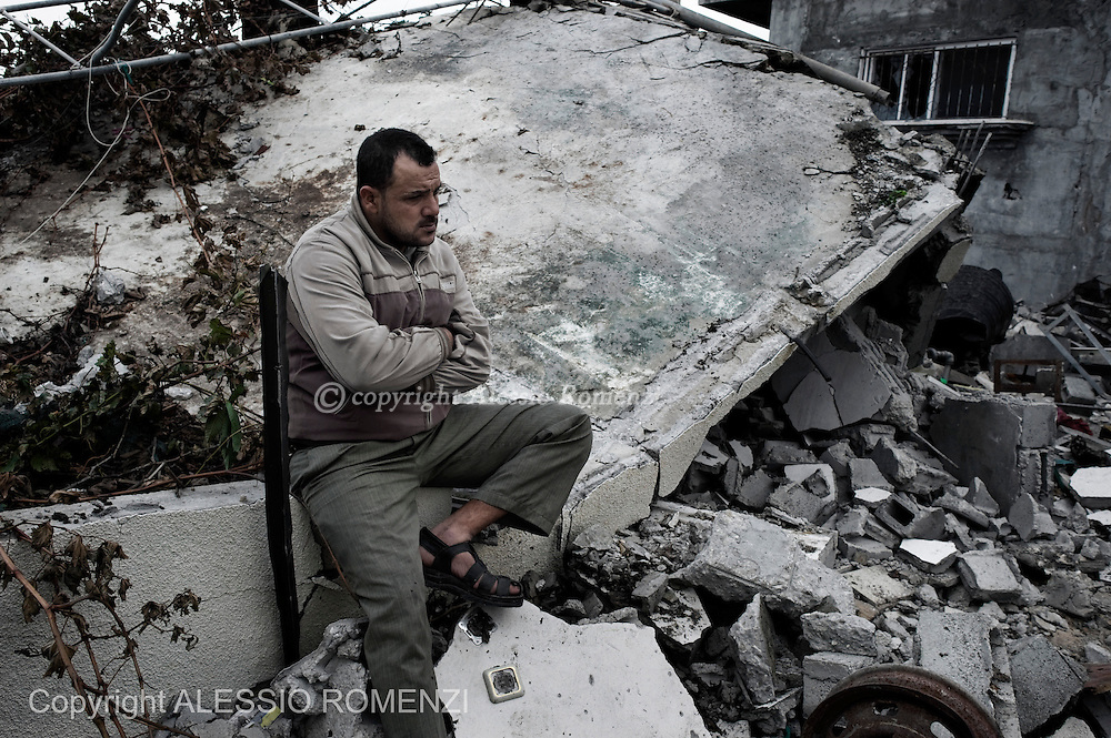 "Gaza Strip: Member of the Palestinian al-Attar family, displaced during the eight-day conflict with Israel, sits on rubbles of his home after  rwas bobed by Israeli airstrike. His house was bombed four years before too, during ""Cast lead"" Israeli Defense Force operation. ALESSIO ROMENZI"