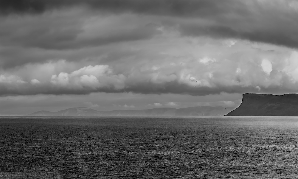 View of the Mull of Kintyre and Fair Head from Ballycastle. The dramatic sky and birds flying overhead made this a good candidate for a black and white conversion, giving a nice dramatic image.<br /> <br /> Image composed of 5 photos at 85mm offering stunning levels of detail, including the cliffs and some houses on the Mull of Kintyre which is around 20 miles away.