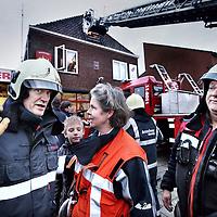Nederland, Landsmeer , 4 januari 2014.<br /> <br /> Op zaterdag 4 januari 2014 draagt burgemeester Astrid Nienhuis van Landsmeer in het kader van de regionalisering het korps van de gemeentelijke brandweer Landsmeer over aan Frank Kuntz, plaatsvervangend regionaal brandweercommandant van de Veiligheidsregio Zaanstreek-Waterland. Dit gebeurt op ludieke wijze tijdens de nieuwjaarsreceptie van de brandweer in de kazerne aan de Fuutstraat in Landsmeer.<br /> Met de overdracht nemen Hoofdbrandwacht Henry de Geus en Brandmeester IJsbrand Wals na 35 dienstjaren afscheid van de vrijwillige brandweer. Ter gelegenheid hiervan worden zij Koninklijk Onderscheiden met de Vrijwilligersmedaille Openbare Orde en Veiligheid. Daarnaast ontvangen twaalf brandweervrijwilligers deze middag de Zilveren Zwaan van de gemeente Landsmeer als dank dat zij zich jarenlang voor de inwoners van de gemeente Landsmeer hebben ingezet, ook bij evenementen in de dorpen.<br /> Op de foto : Brandmeester IJsbrand Wals (l) in gesprek met  Astrid Nienhuis, burgemeester van Landsmeer.<br /> Foto:Jean-Pierre Jans