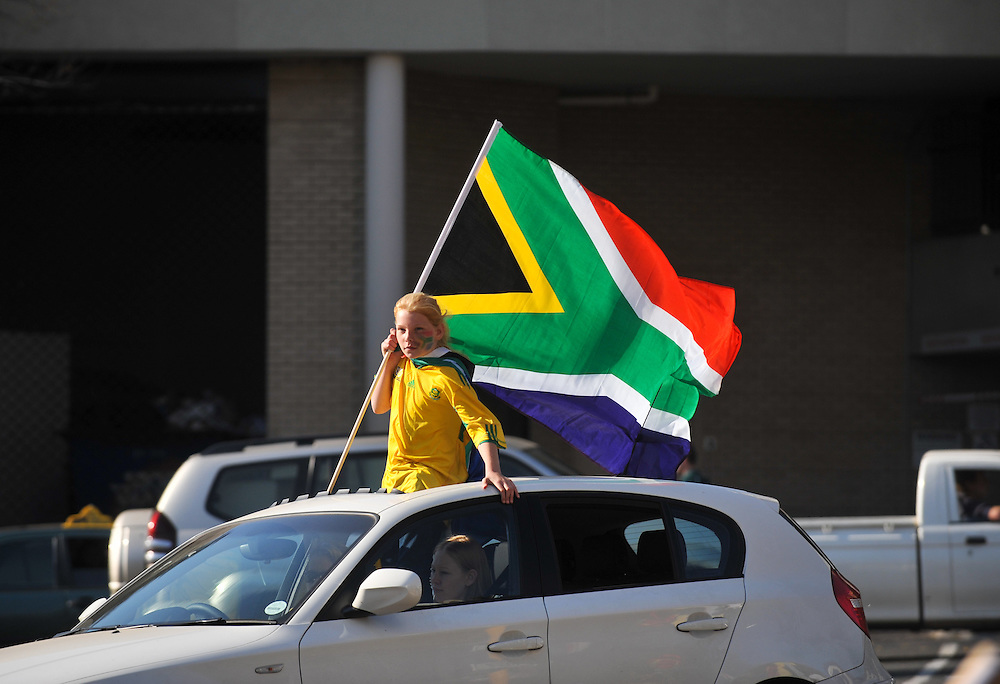 """A girl holds the South African flag out the car as she leaves following the """"United We Shall Stand"""" rally for the South African national soccer team, Bafana Bafana, Tuesday, June 9, 2010 in Johannesburg, South Africa. South Africa is hosting the FIFA World Cup, which begins June 11. Photo by Bahram Mark Sobhani"""