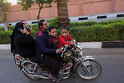 A family of rive ride fast on a motorbike on a road in modern Luxor, Nile Valley, Egypt.