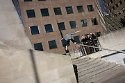 Onlookers watch a young skateboarder flying through the air during his acrobatic jump down steps.
