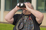 New Paltz, New York - A man watches the Transit of Venus through filtered binoculars on the SUNY New Paltz campus on June 5, 2012. Venus crossed in front of the sun and was visible as a small black disk. The next Venus transit will not occur until 2117.